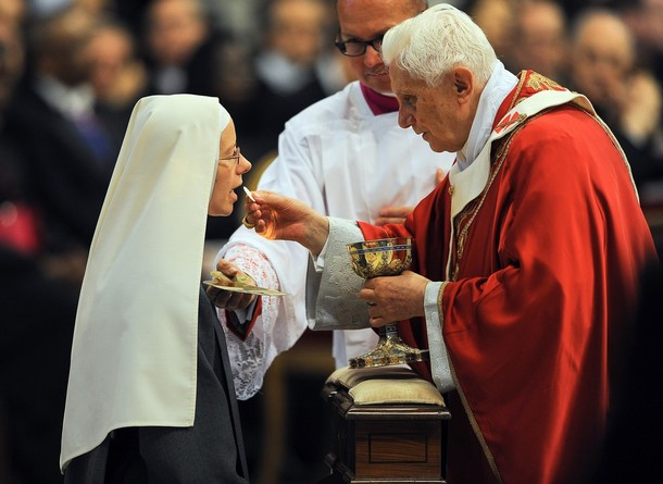 Pope Benedict XVI gives communion to a n